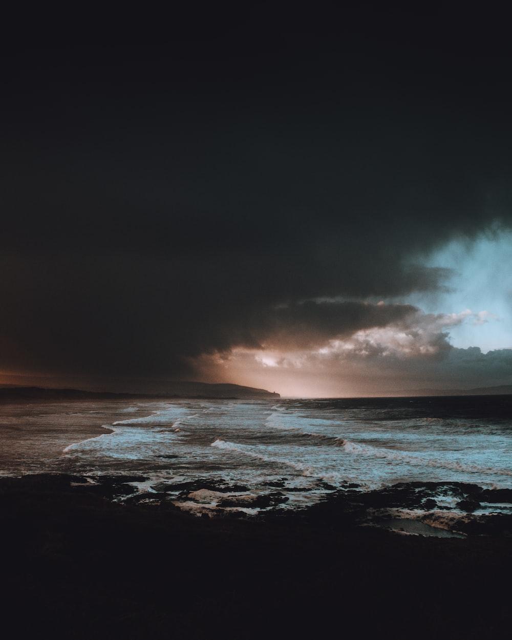 body of water under dark clouds