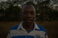 closeup photo of man wearing blue and white shirt