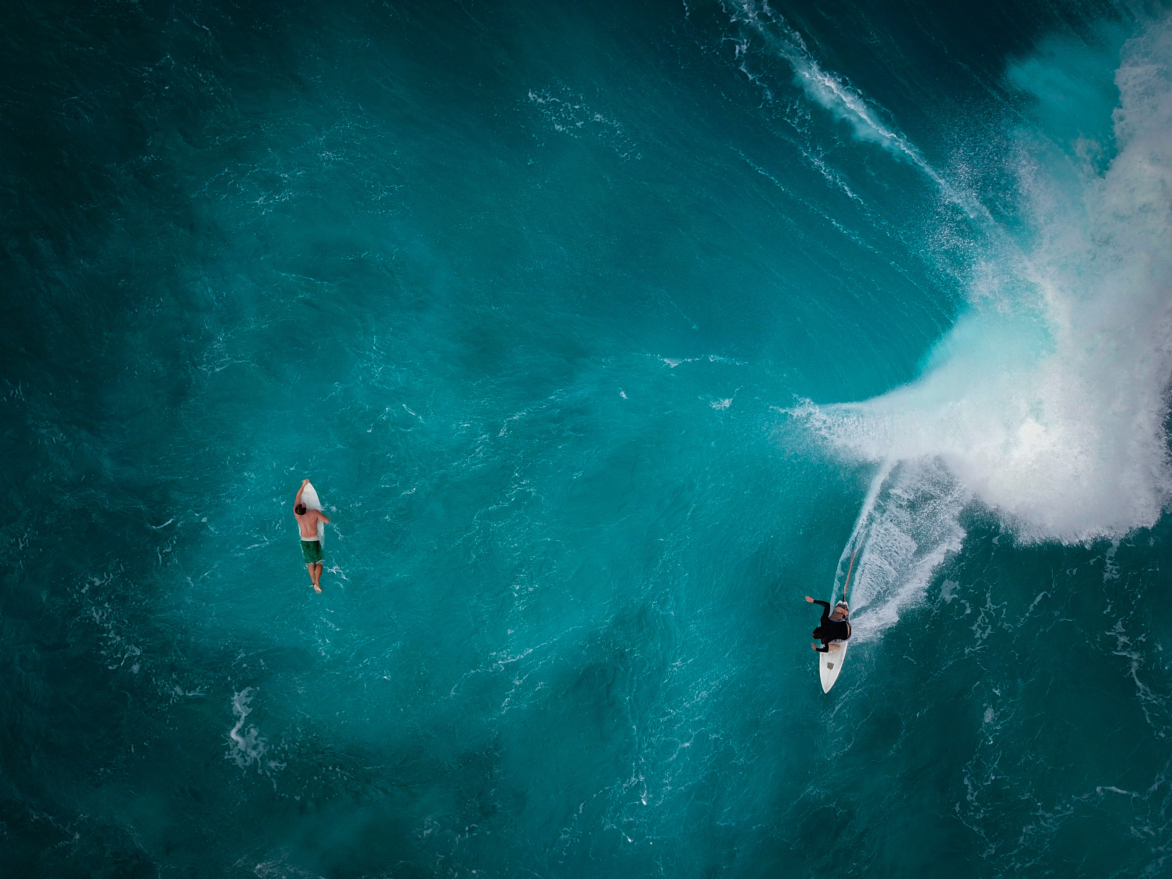 aerial photography of two persons surfing