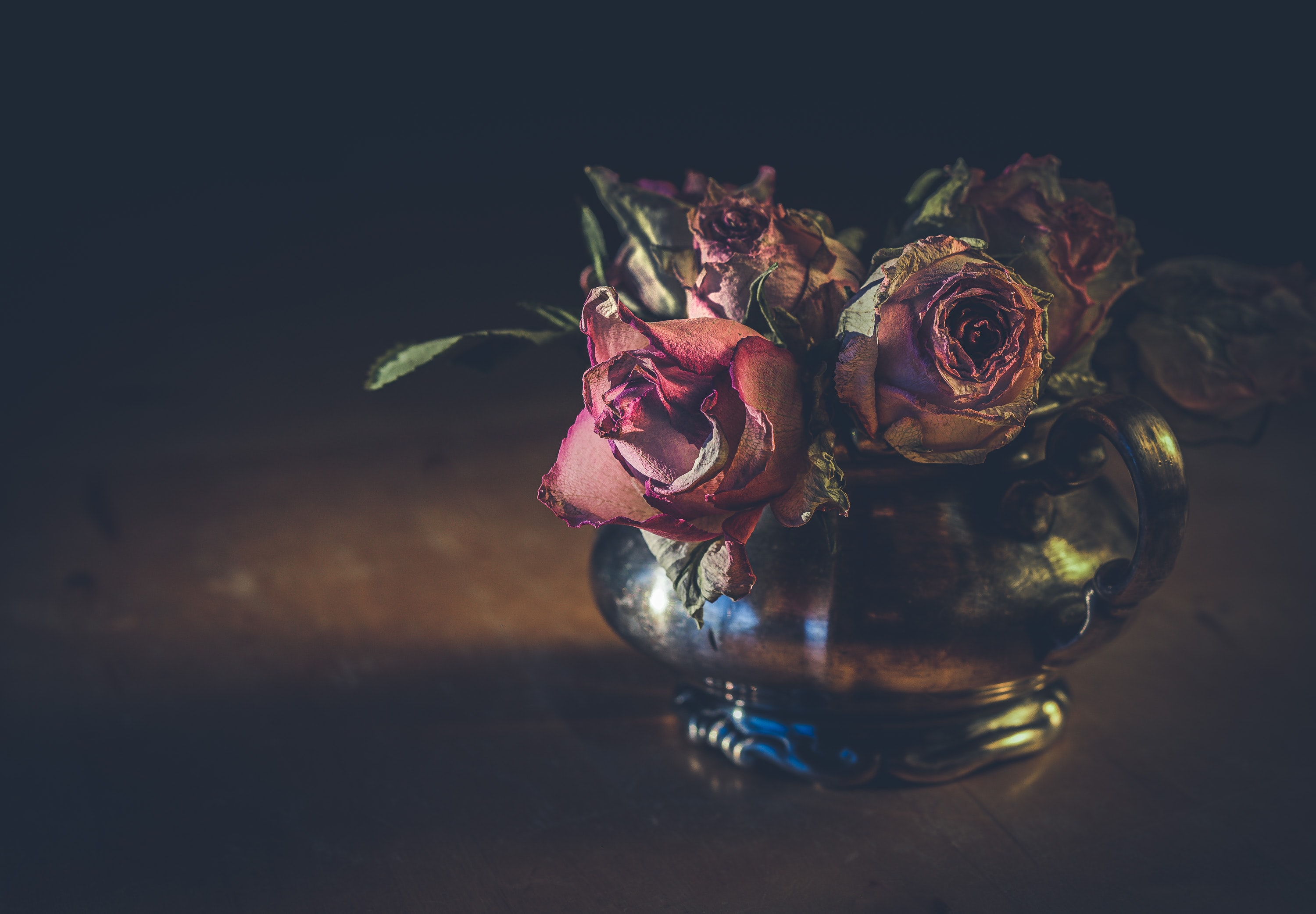 withered roses in clear glass vase