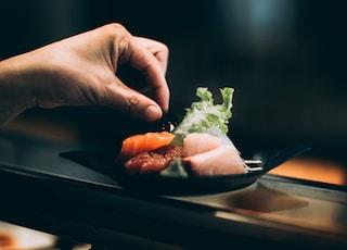 left hand picking vegetable on plate
