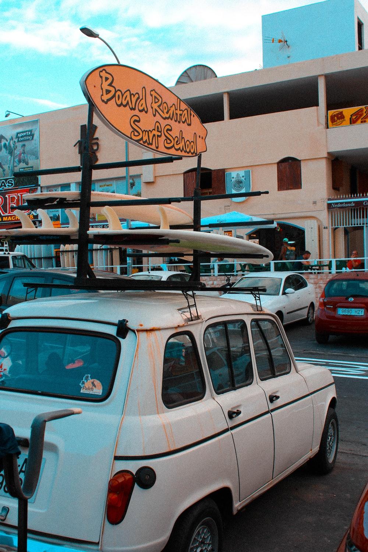 parked white vehicle near beige concrete building