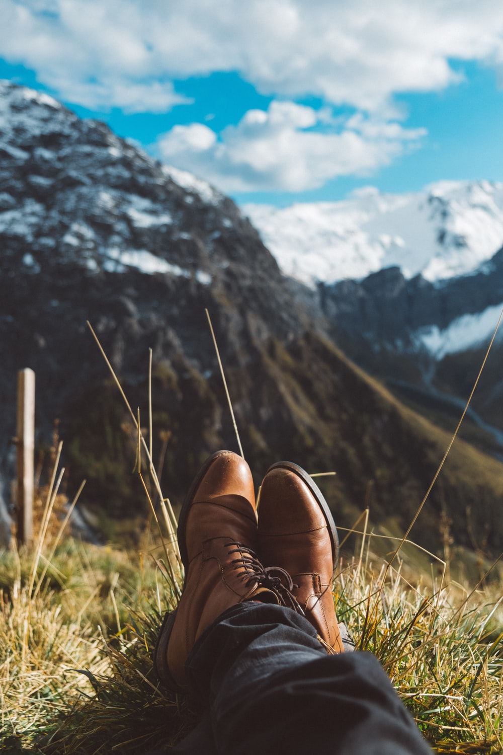 selective focus photo of person wearing brown dress shoes near mountains