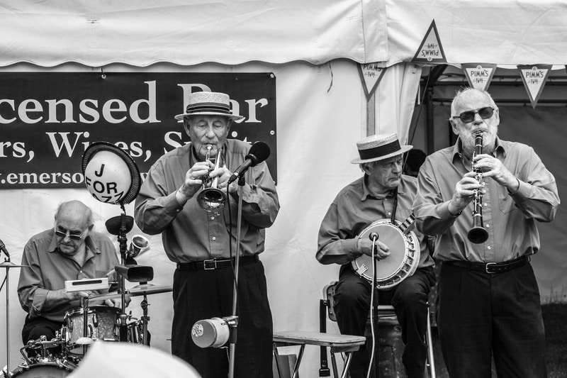 grayscale photo of group of people playing on stage