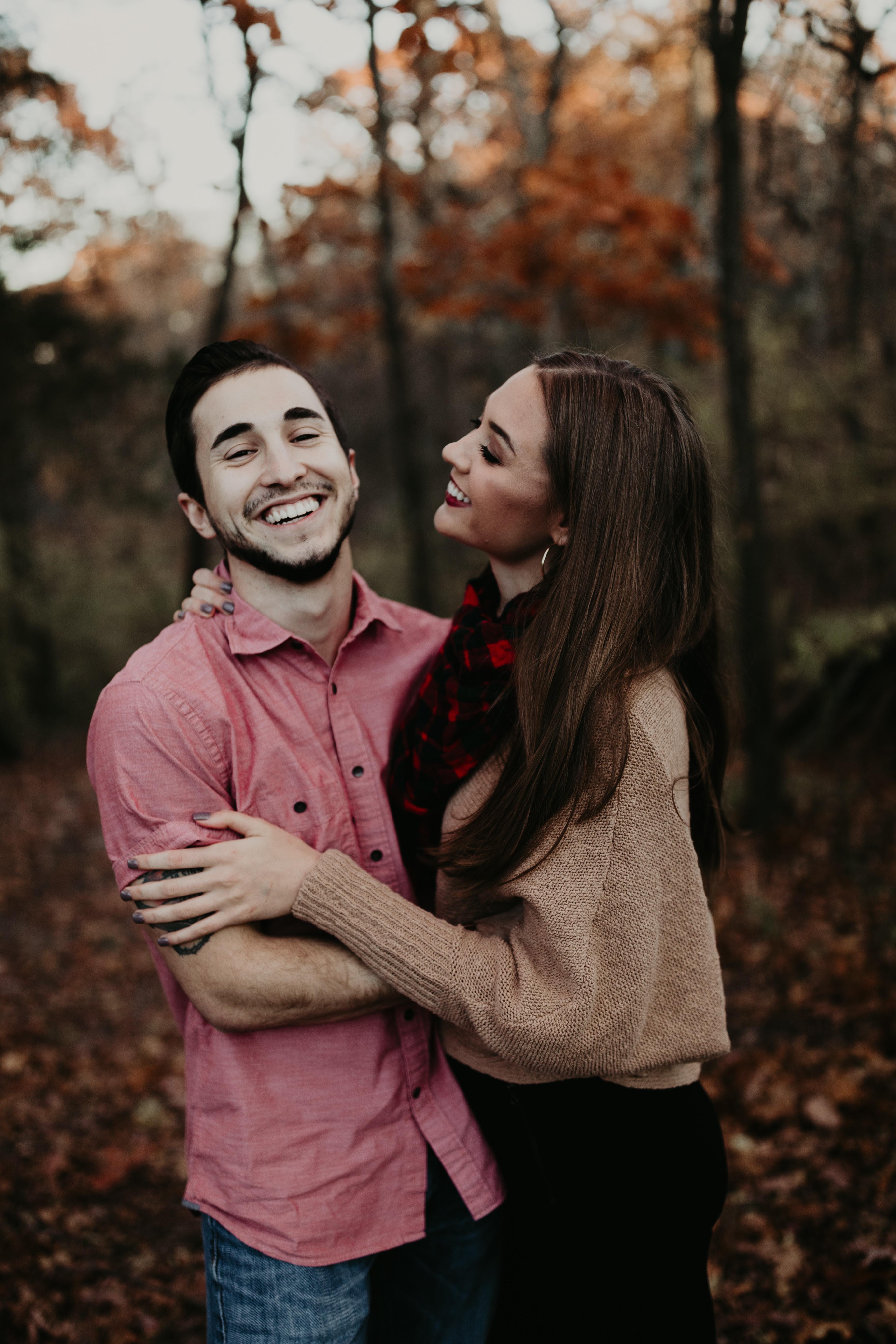 woman hugging man selective focus photography