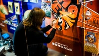 woman sitting wearing black sweater holding Chicinnati Bengals poster
