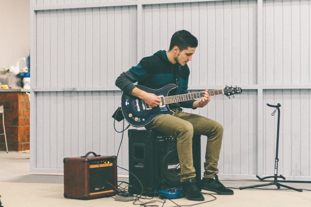 man sitting in guitar amplifier while playing guitar at daytime