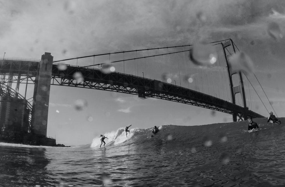 grayscale people surfing under bridge