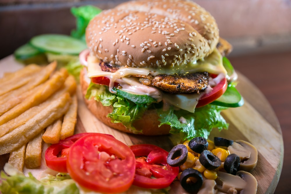 hamburger with vegetables and meat beside French fries