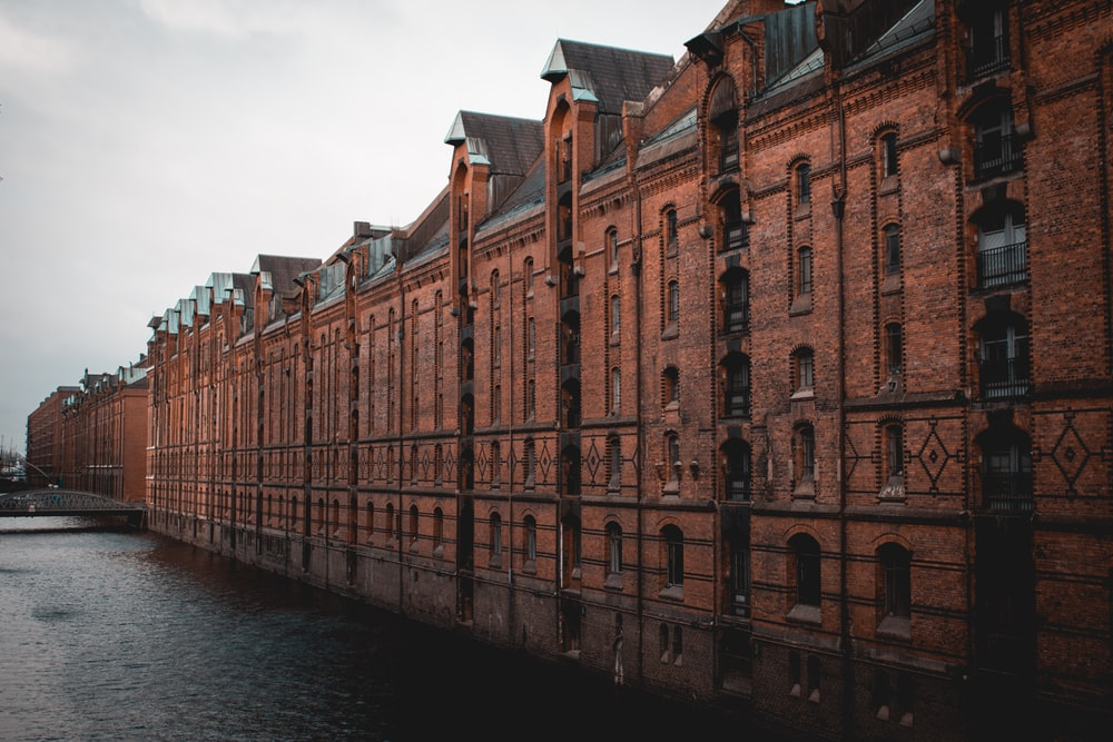 photo of brown building beside body of water