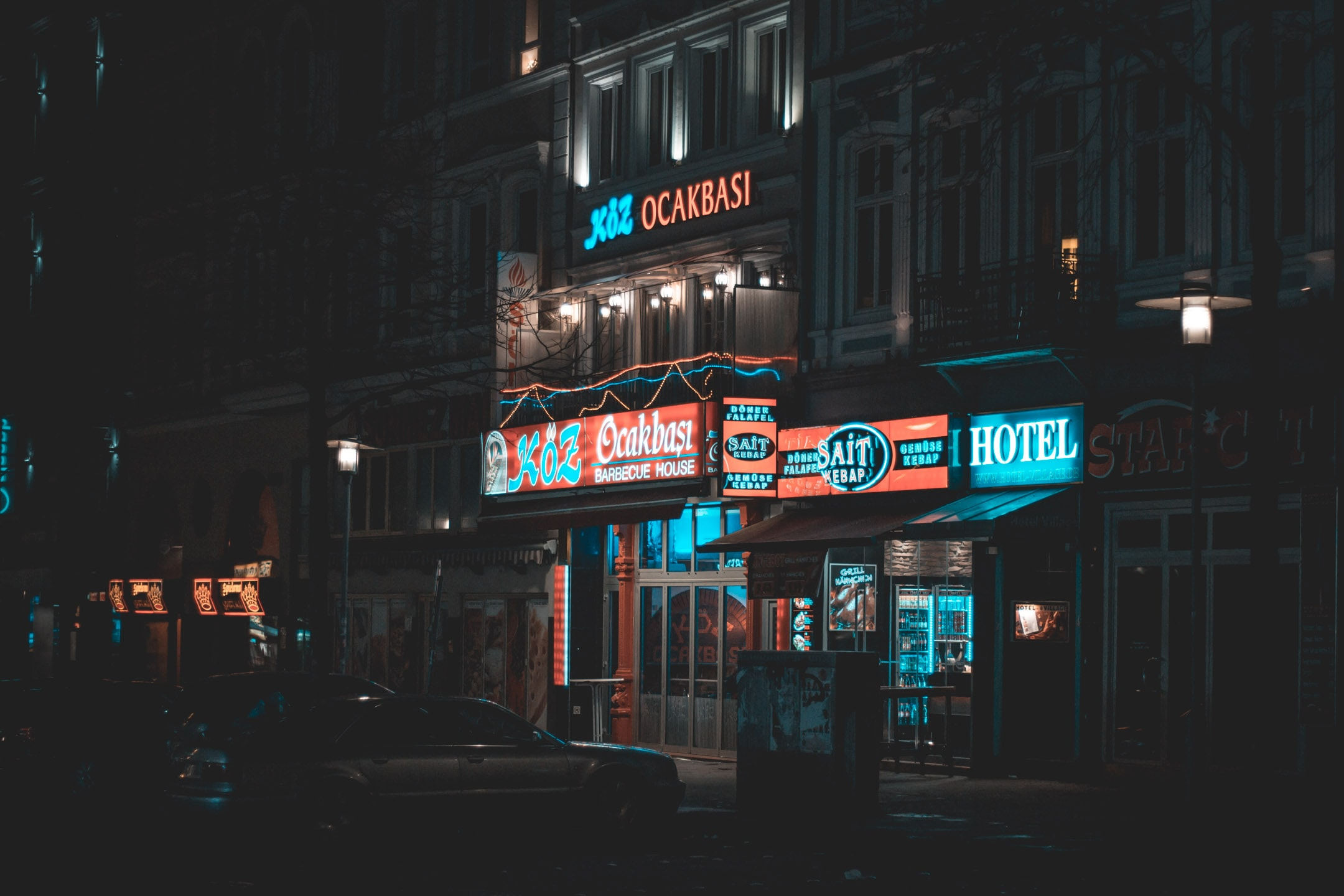 sedan parked near building with neon signage turned on at nighttime