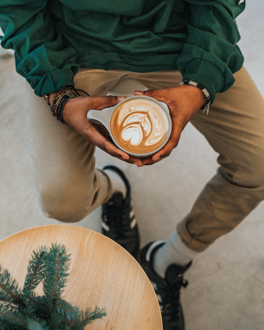 person holding cup with designed coffee