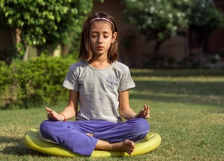 girl performing meditation on yellow seat outdoors