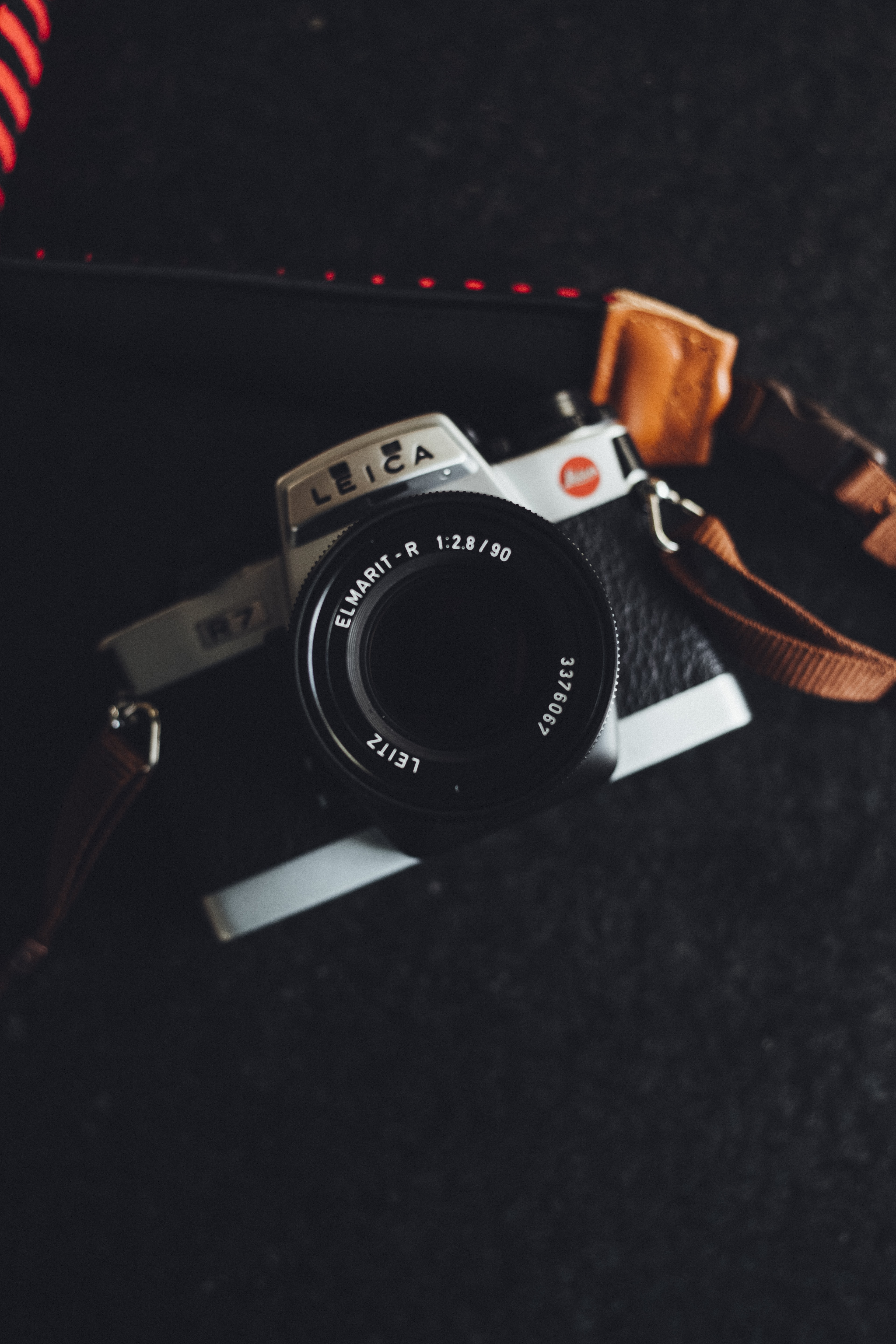 black and gray Leica bridge camera with brown sling on top of black textile