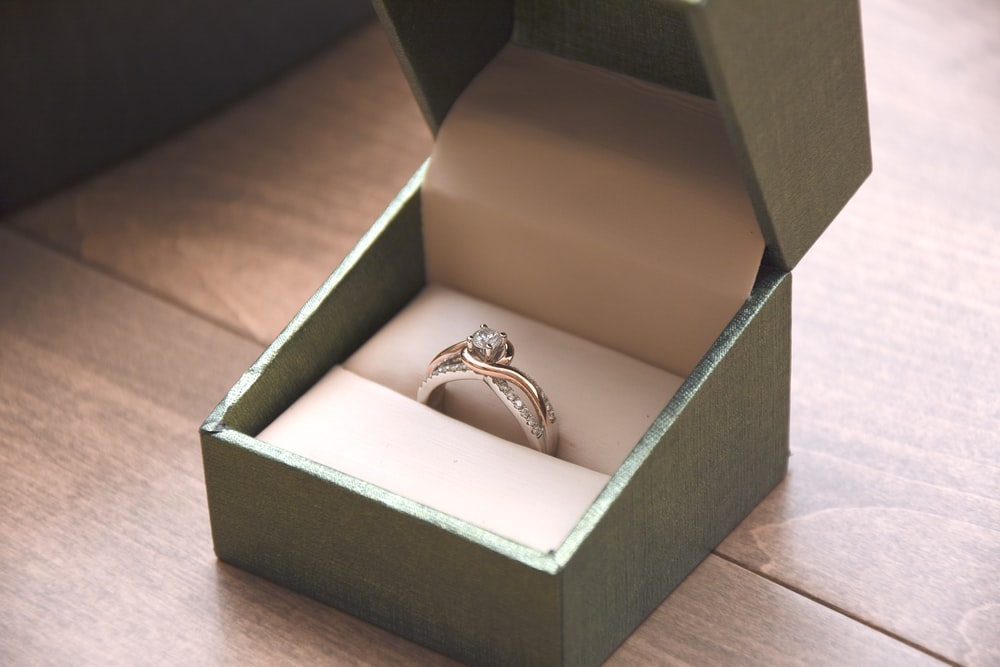 silver-colored ring with gemstone in a box
