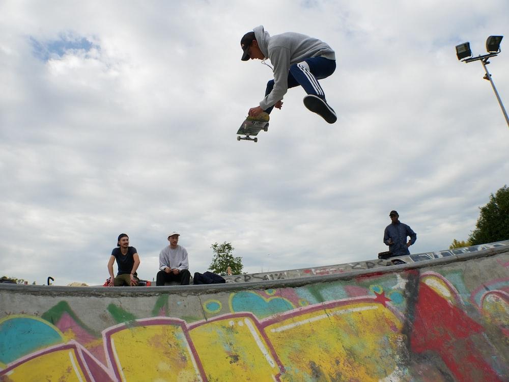 man on air playing skateboard above skateboard ramp at daytime