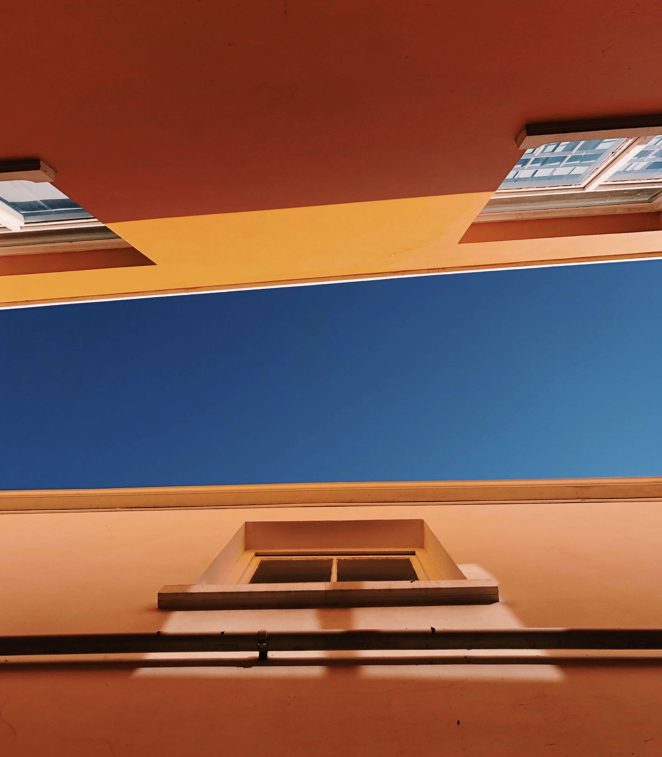 low-angle photography of brown concrete buildings under blue sky at daytime