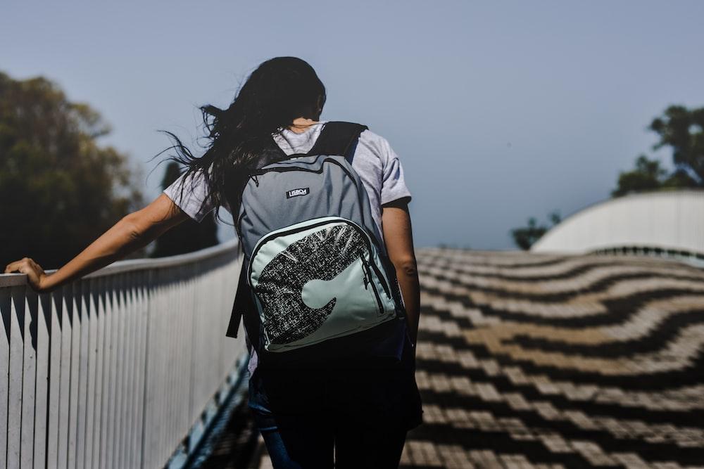 woman walking at bridge wearing backpack