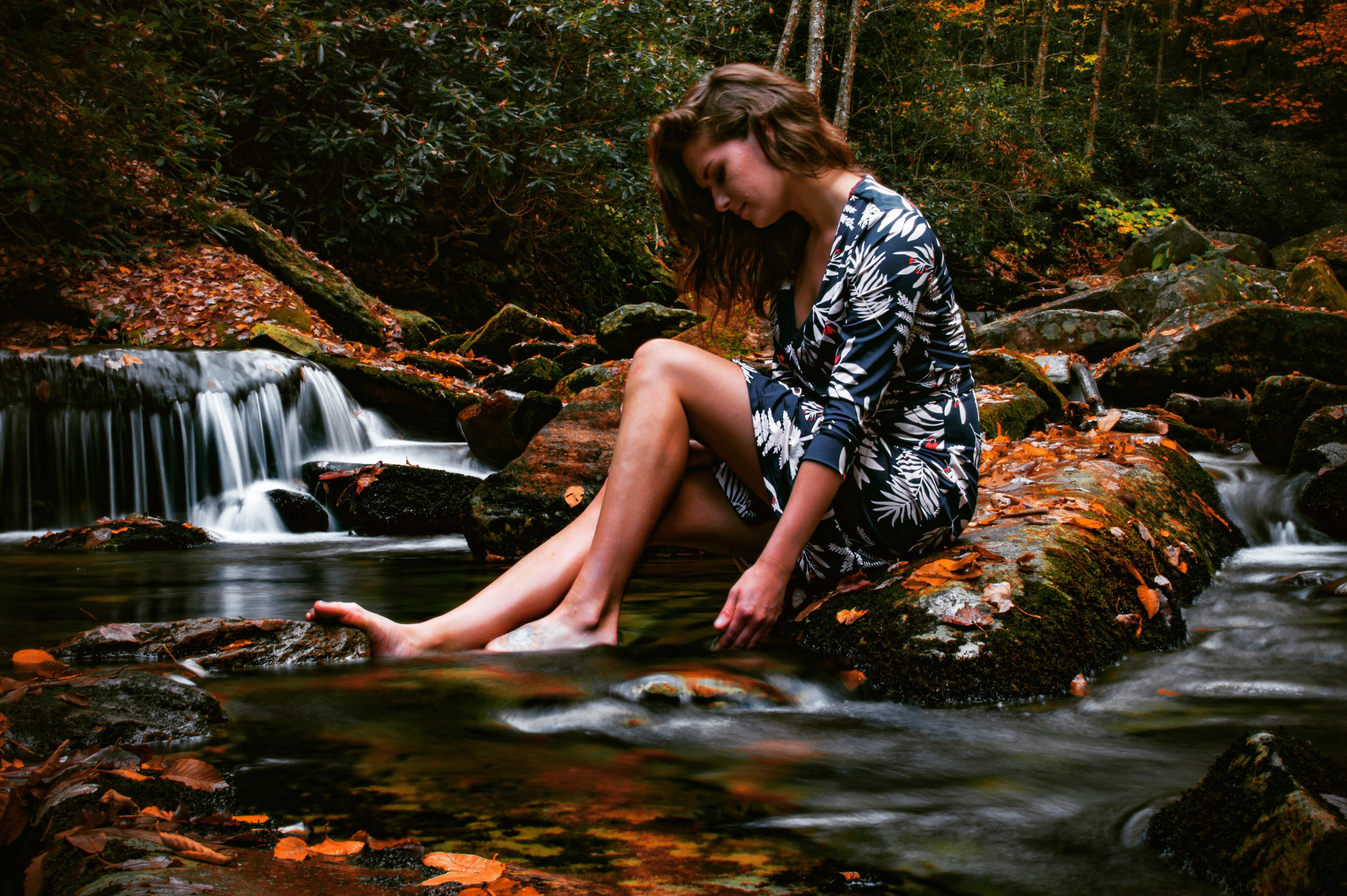 woman sitting on rock near body of water