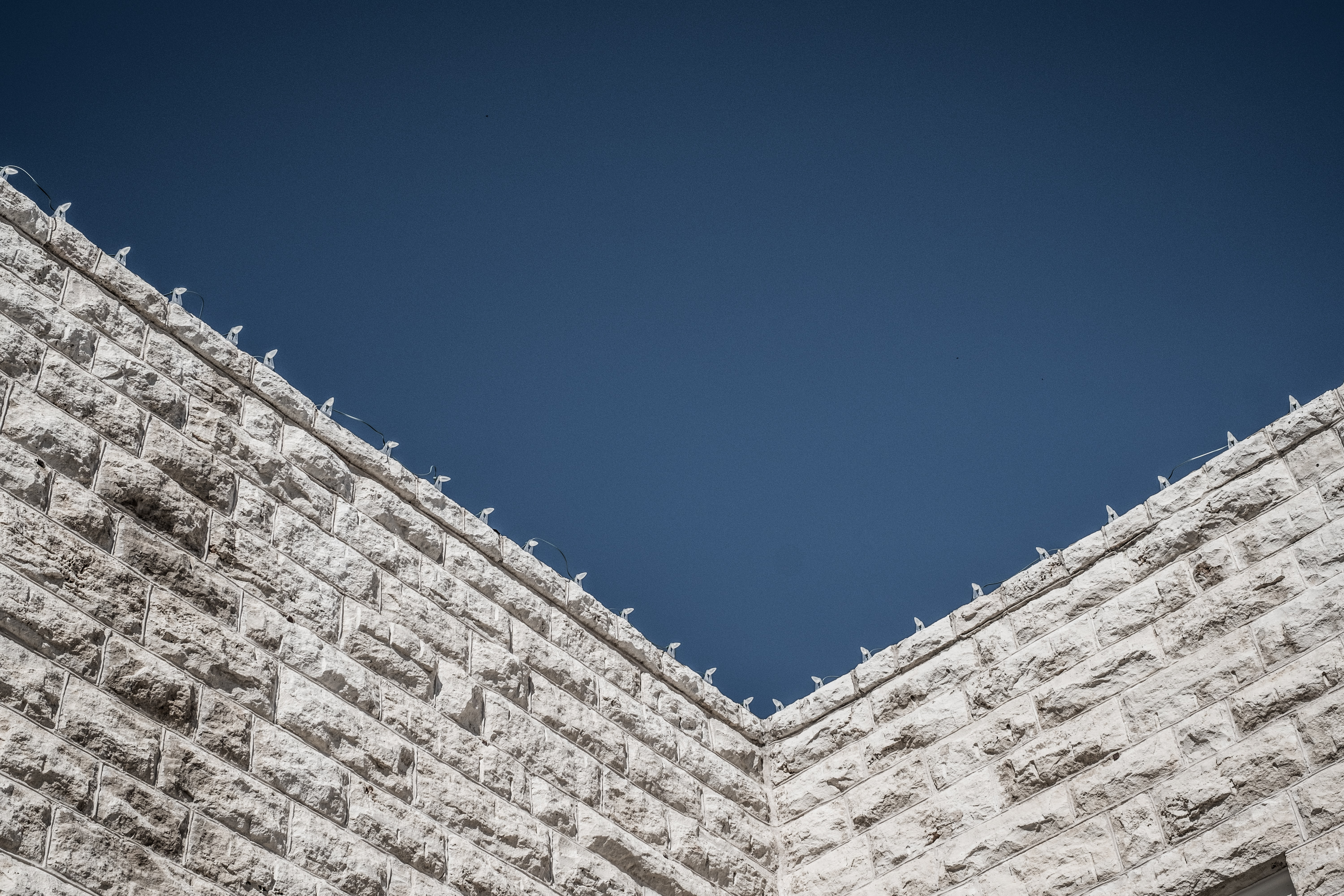 low angle photography of gray concrete wall at daytime