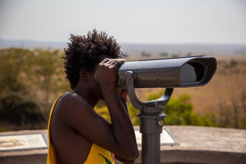 man using coin operated telescope during daytime