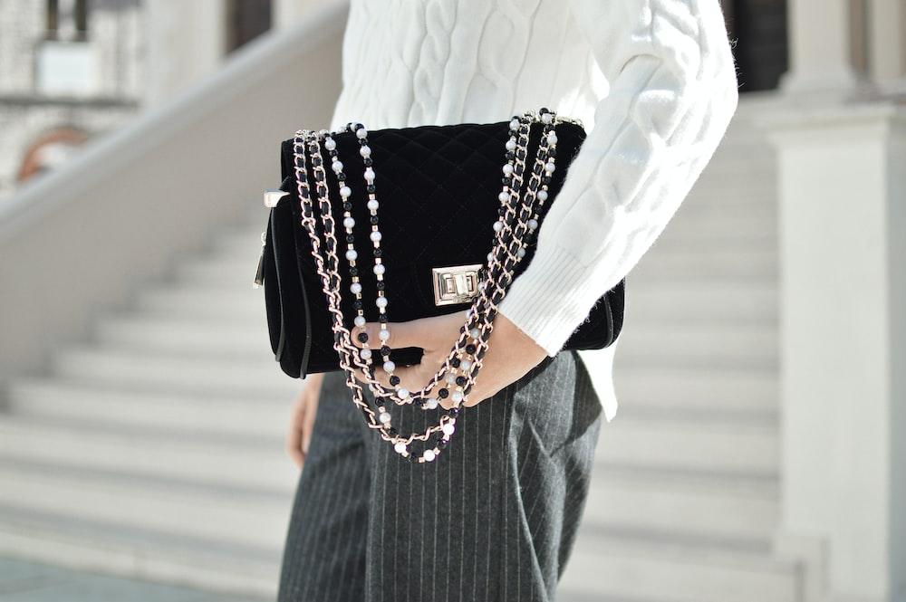 person holding black crossbody bag