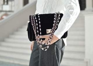 person holding black crossbody bag
