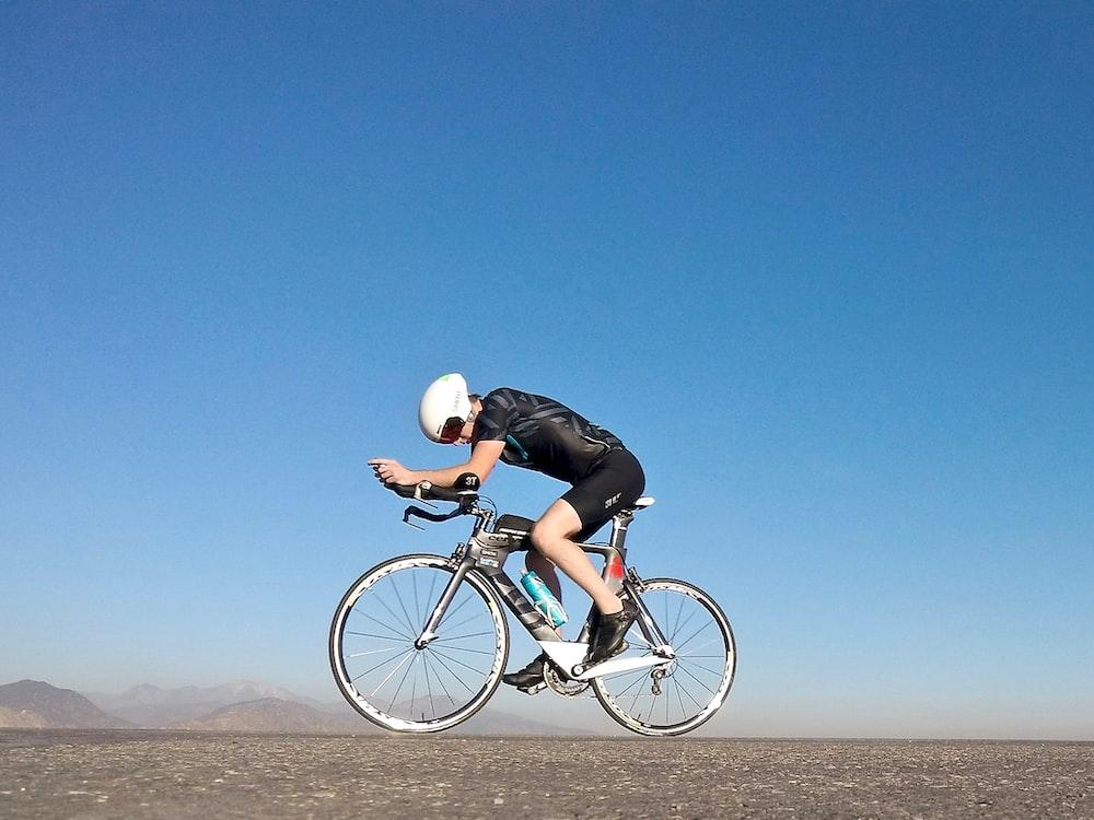 man riding on gray road bicycle during daytime