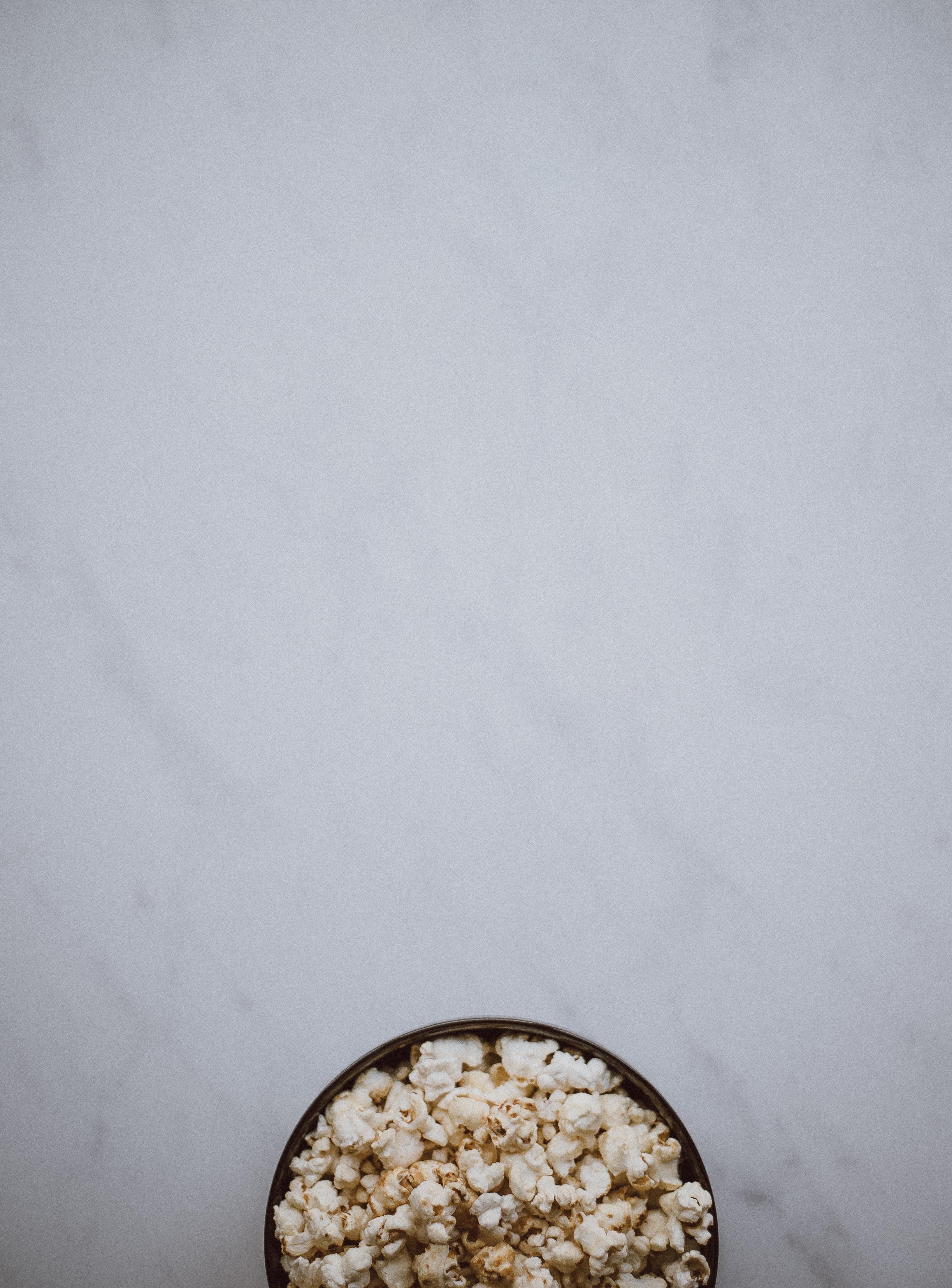 bowl of popcorn on white surface