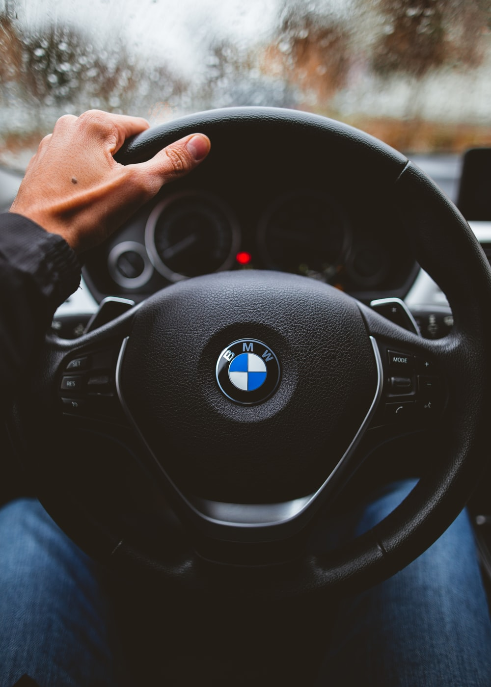 person holding BMW vehicle steering wheel