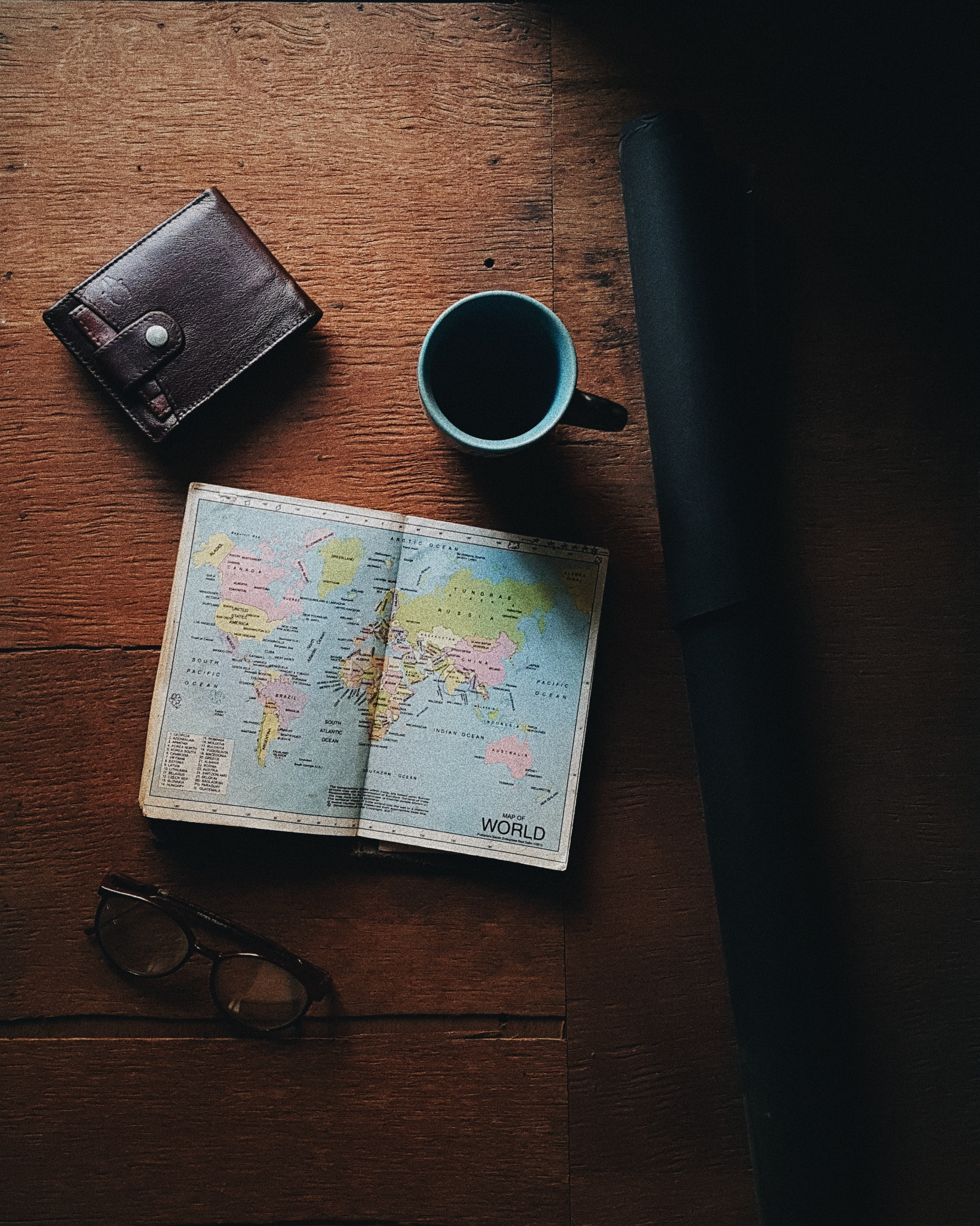 world map beside blue and black ceramic mug