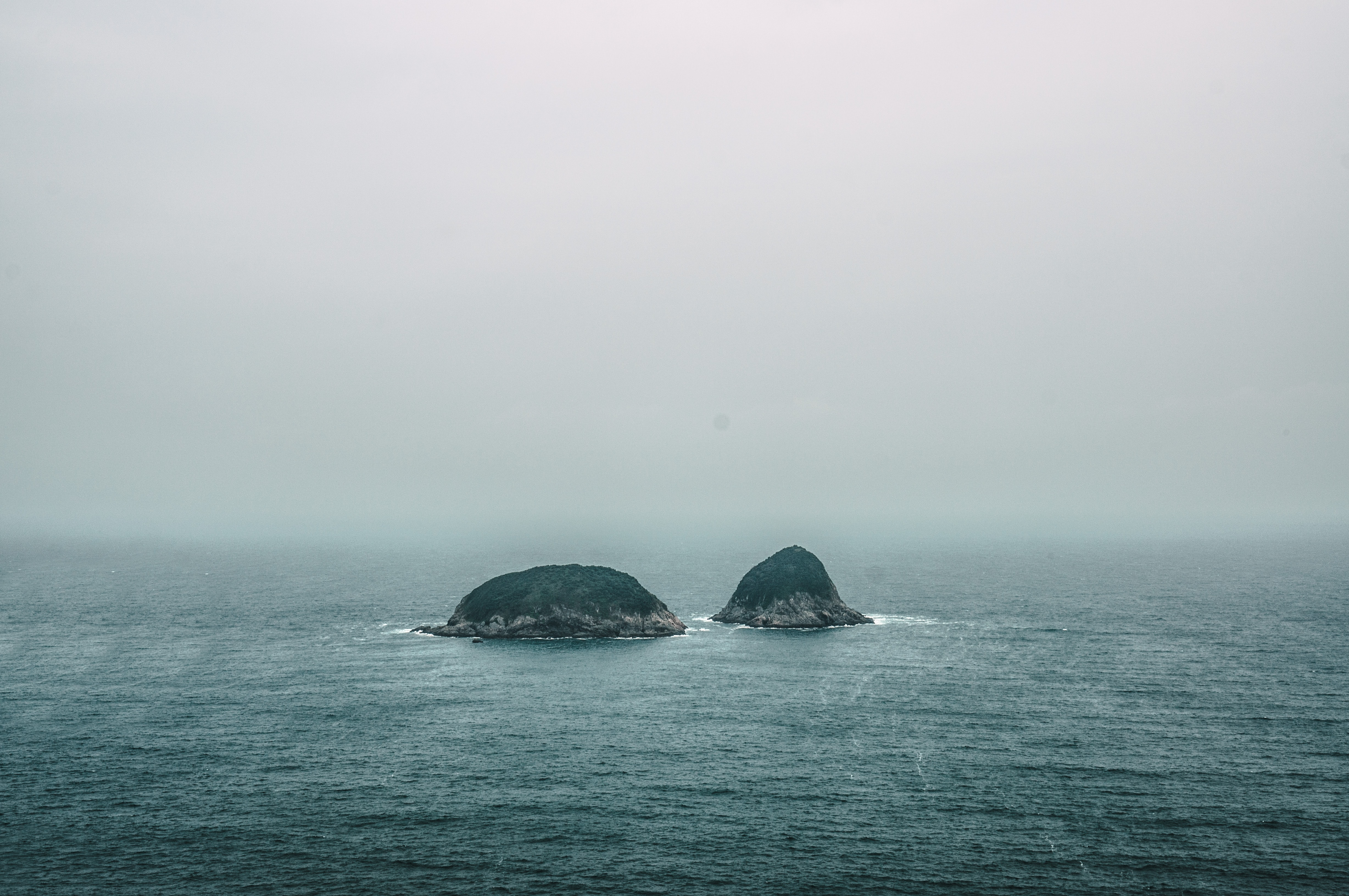 two gray rock formations on the middle of sea at daytime