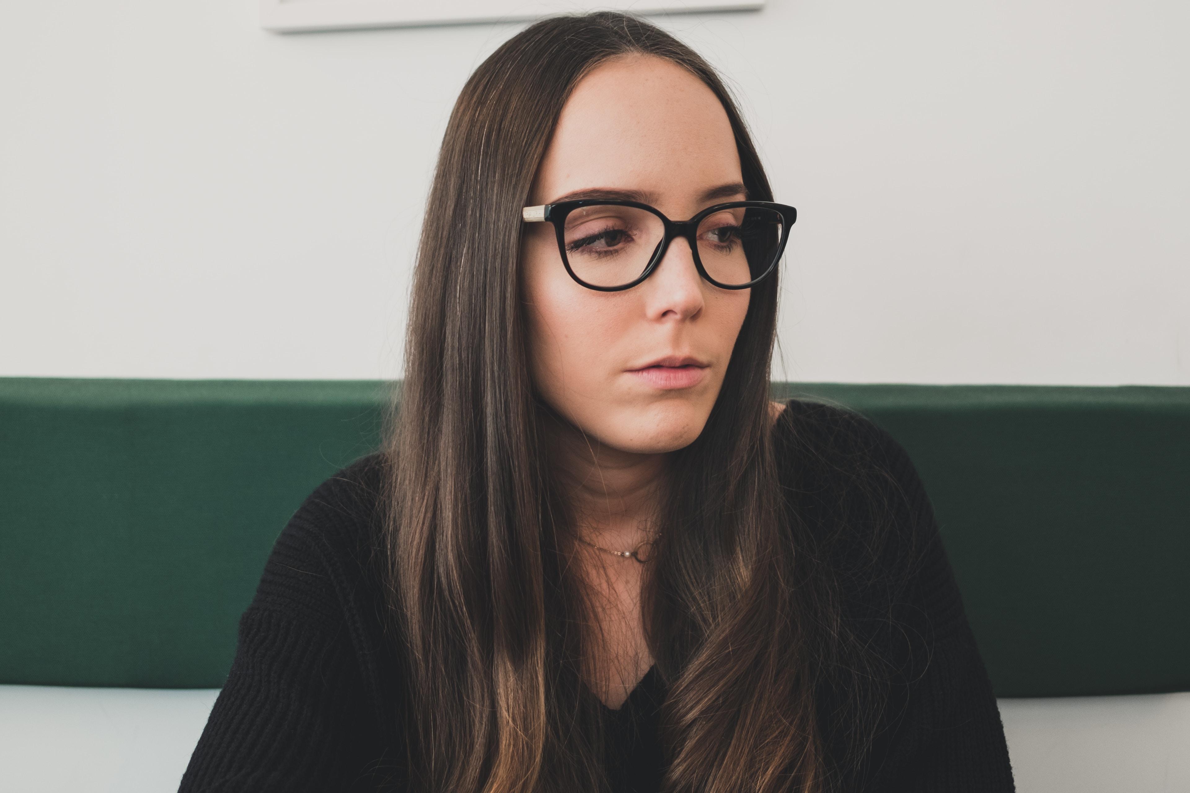 brunette haired woman in black shirt wearing eyeglasses