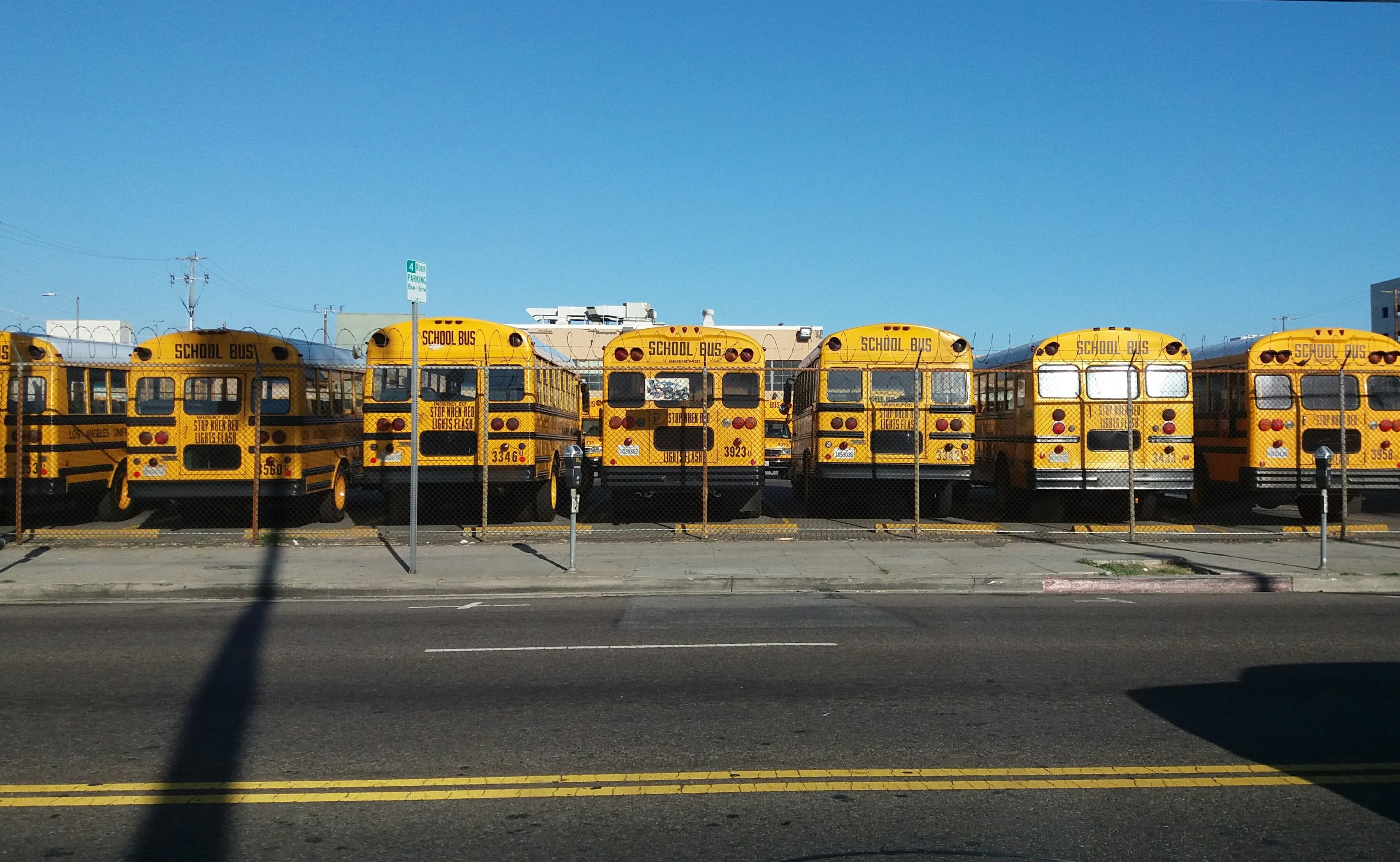 photo of yellow bus park on parking lot