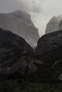 waterfall in the middle of two mountains during a foggy weather