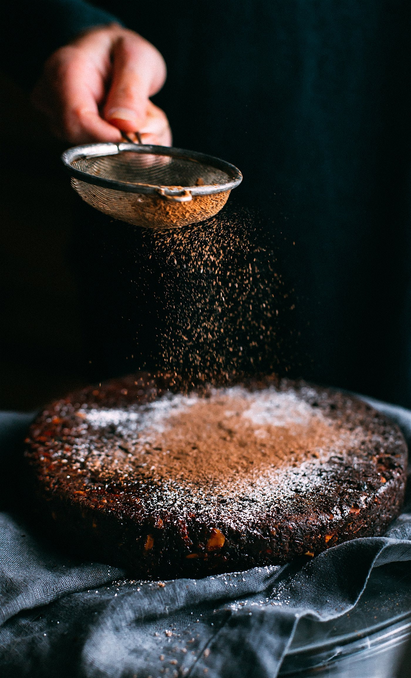 person pouring chocolate powder on cake