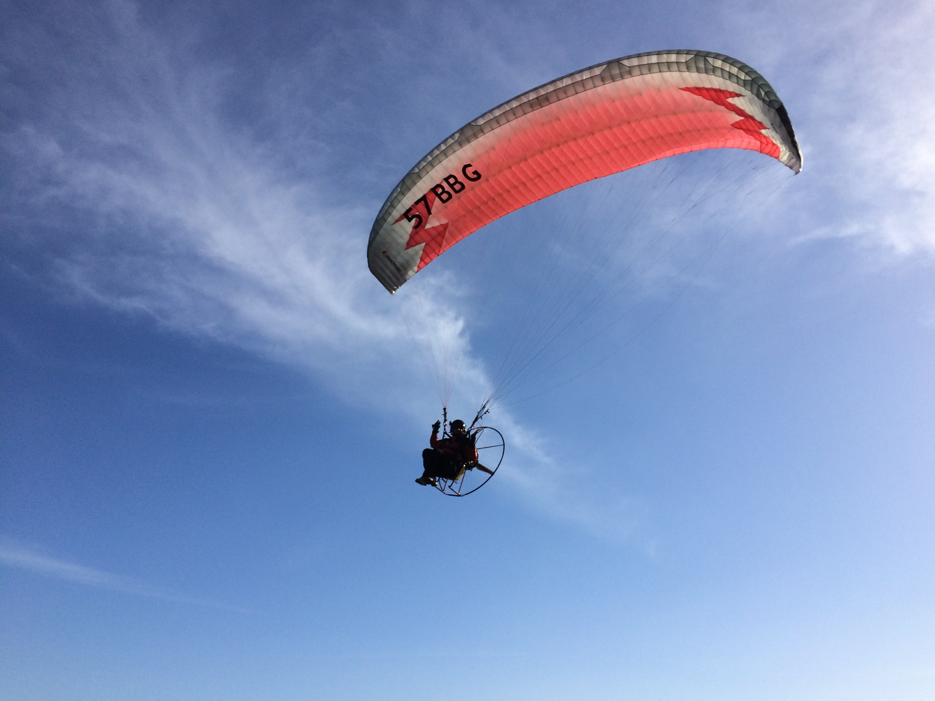 person paragliding under blue sky