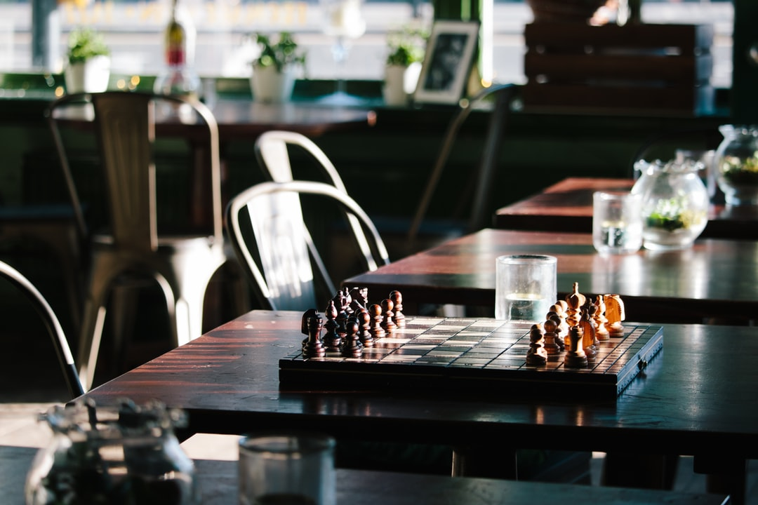 brown and black chess board on brown wooden table