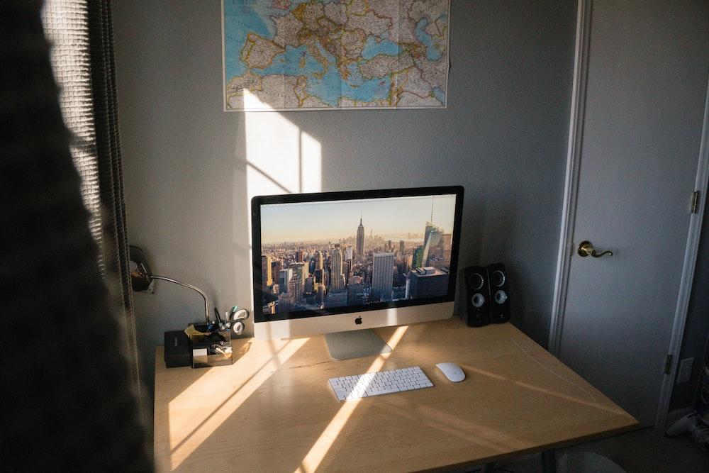 turned on silver iMac on beige wooden desk