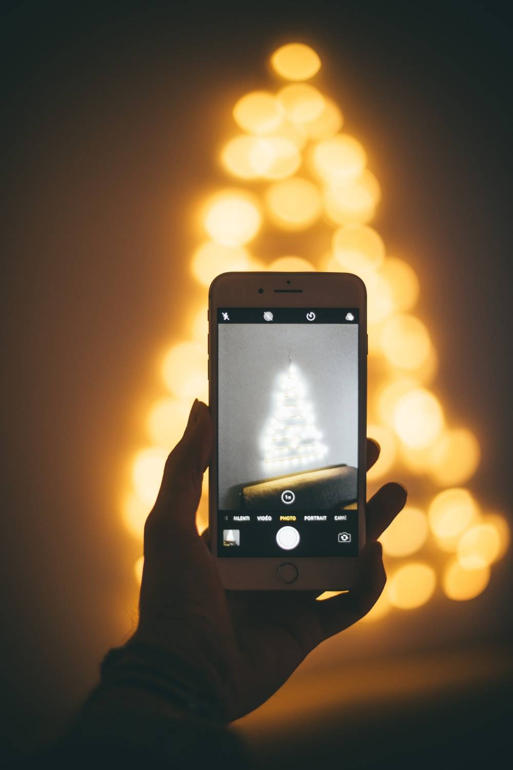 person capturing image of lighted Christmas tree