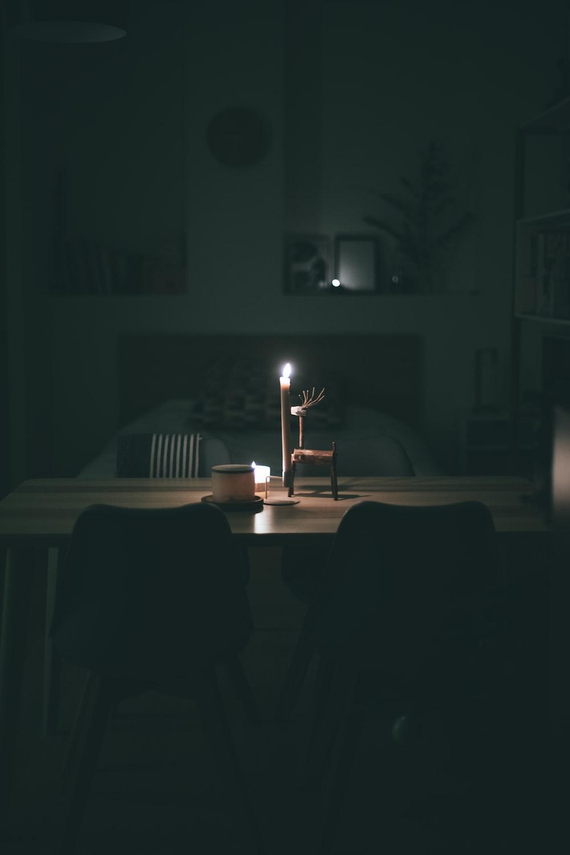 lighted white pillar candle near ceramic mug on wooden table