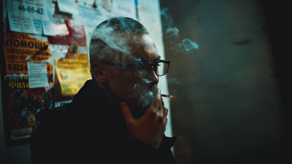 man doing smoke standing beside wall