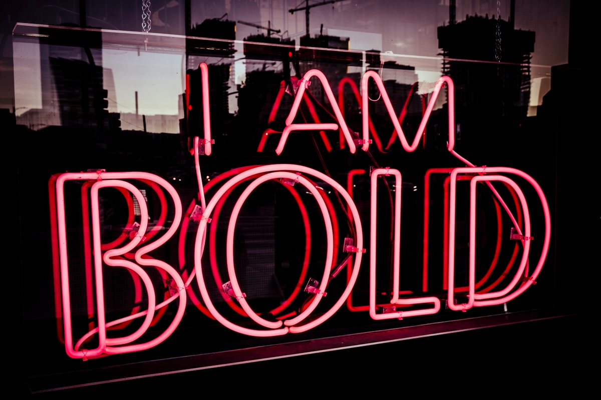 I neon sign against a dark cityscape that says I am Bold.