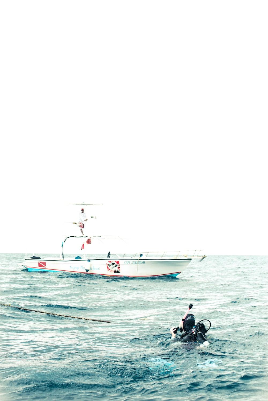 black person scuba diving near white boat