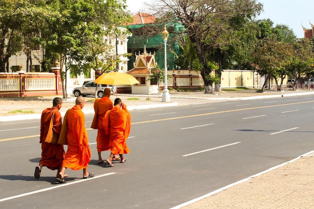 people in orange robe walking on gray asphalt road during daytime