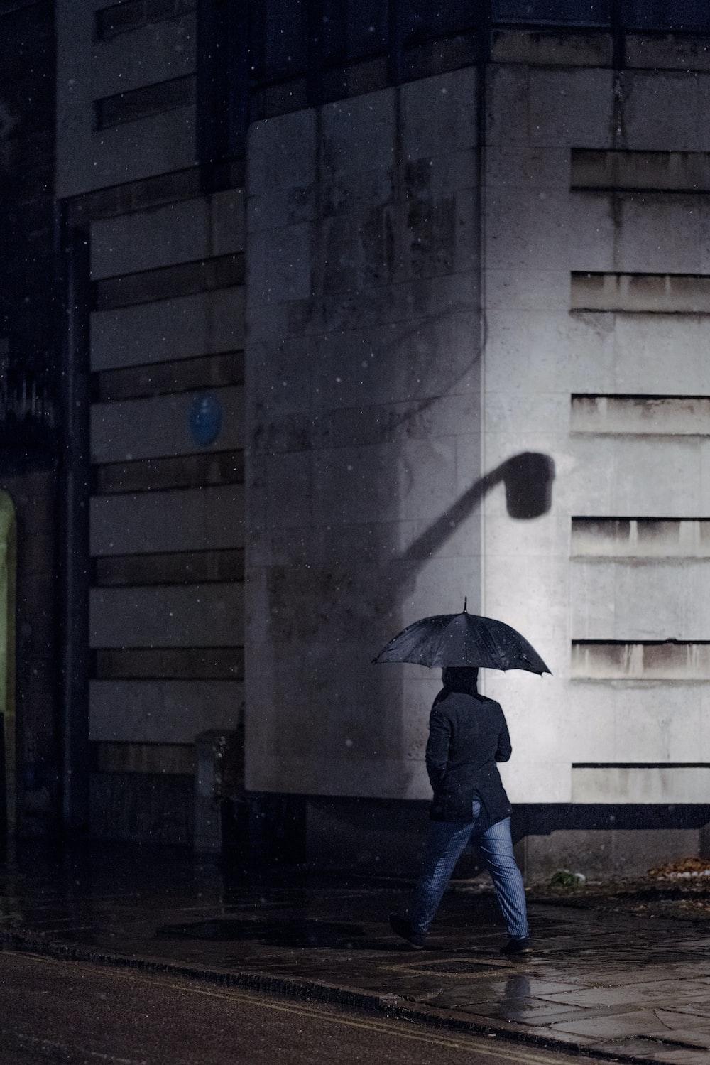 man walking under his umbrella