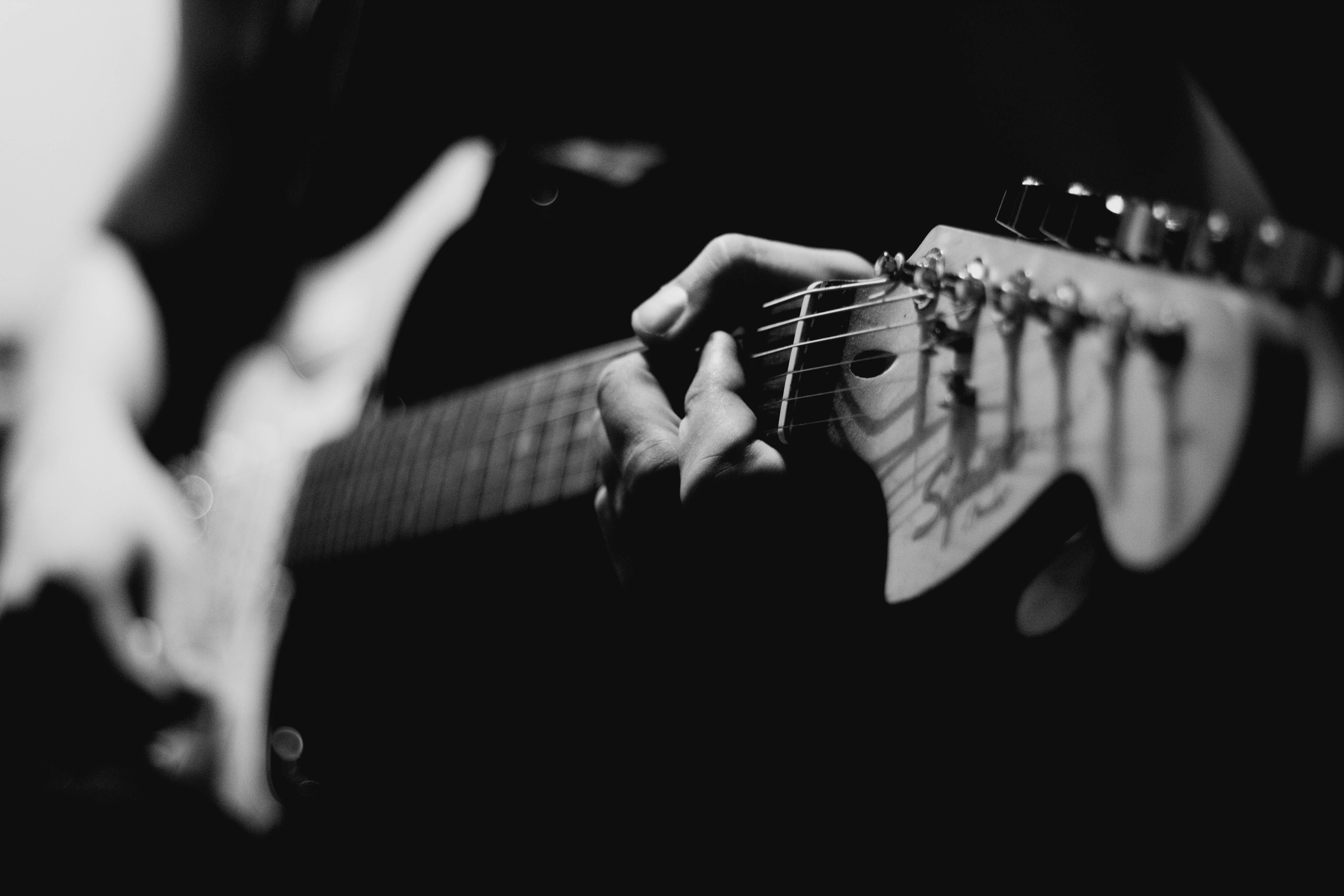 grayscale photography of person playing electric guitar