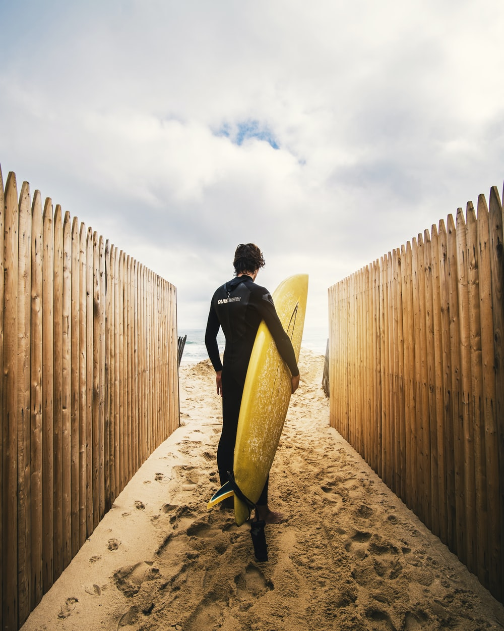 person standing between privacy fences while holding yellow surfboard during daytime