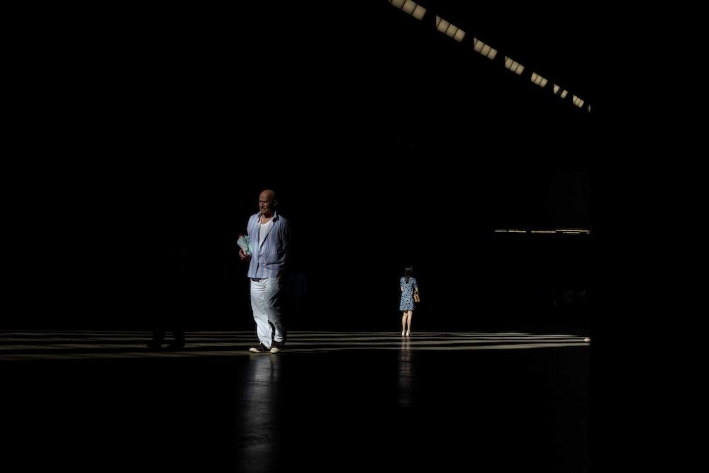 person standing on platform in dark area