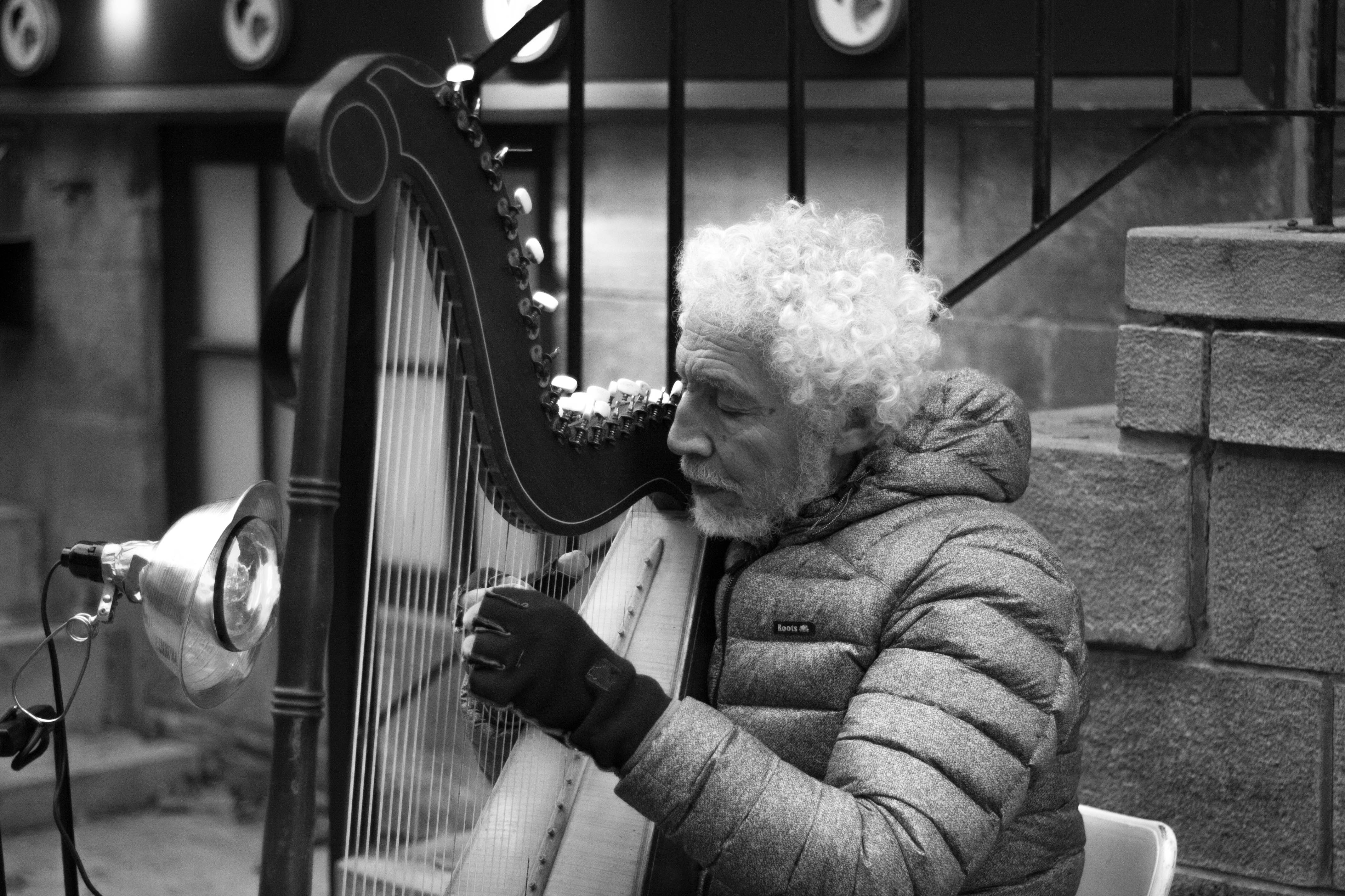 grayscale photo of man playing harp near stairs